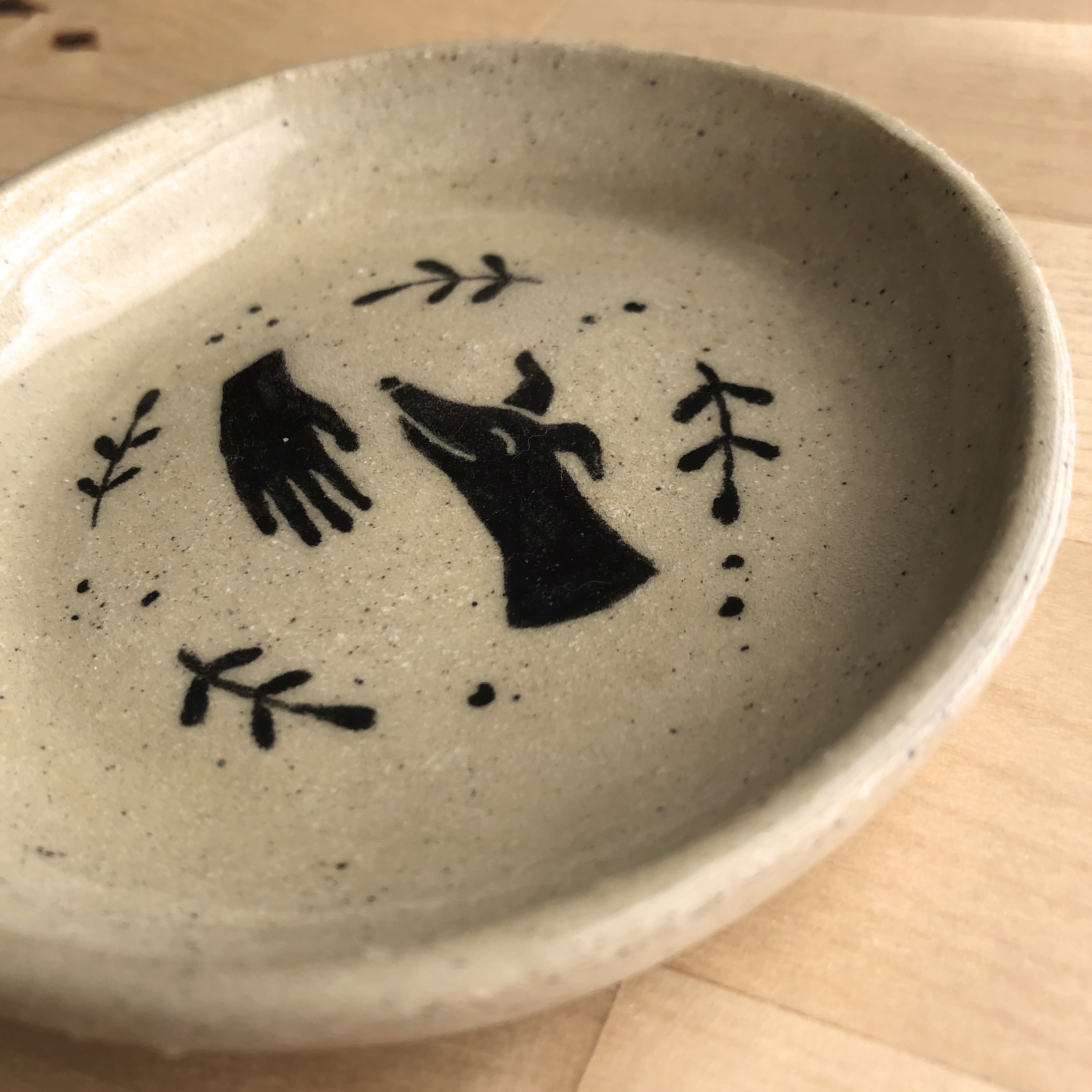 Closeup of a ceramic dish with an illustration of a hand petting a greyhound surrounded by plants