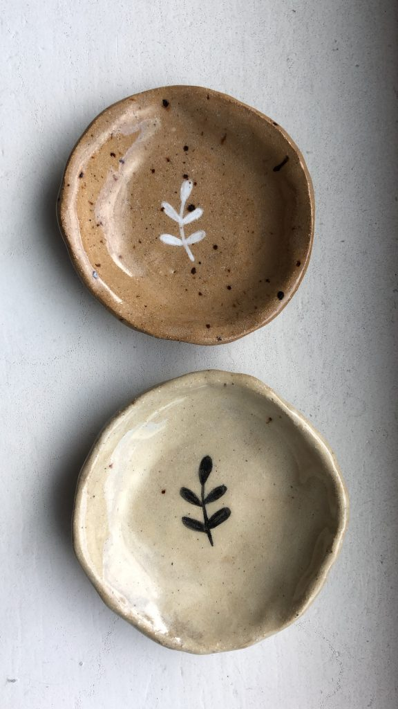 Two small handmade dishes with small branch illustrations painted on
