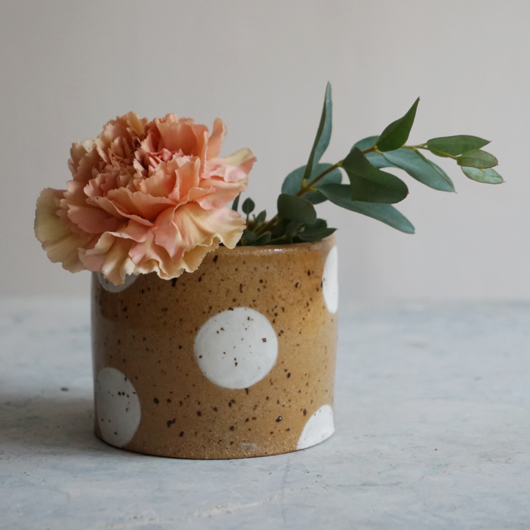 A polka dotted ceramic tumbler with a flower and some greenery in it
