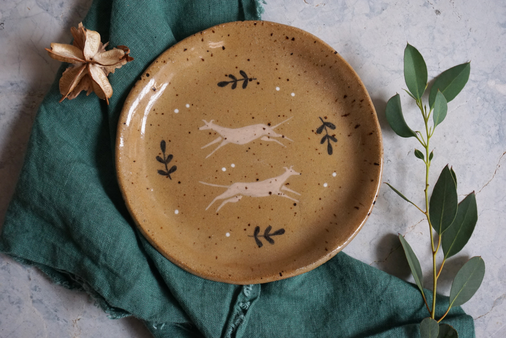 A ceramic plate with an illustration of two greyhounds and leaves