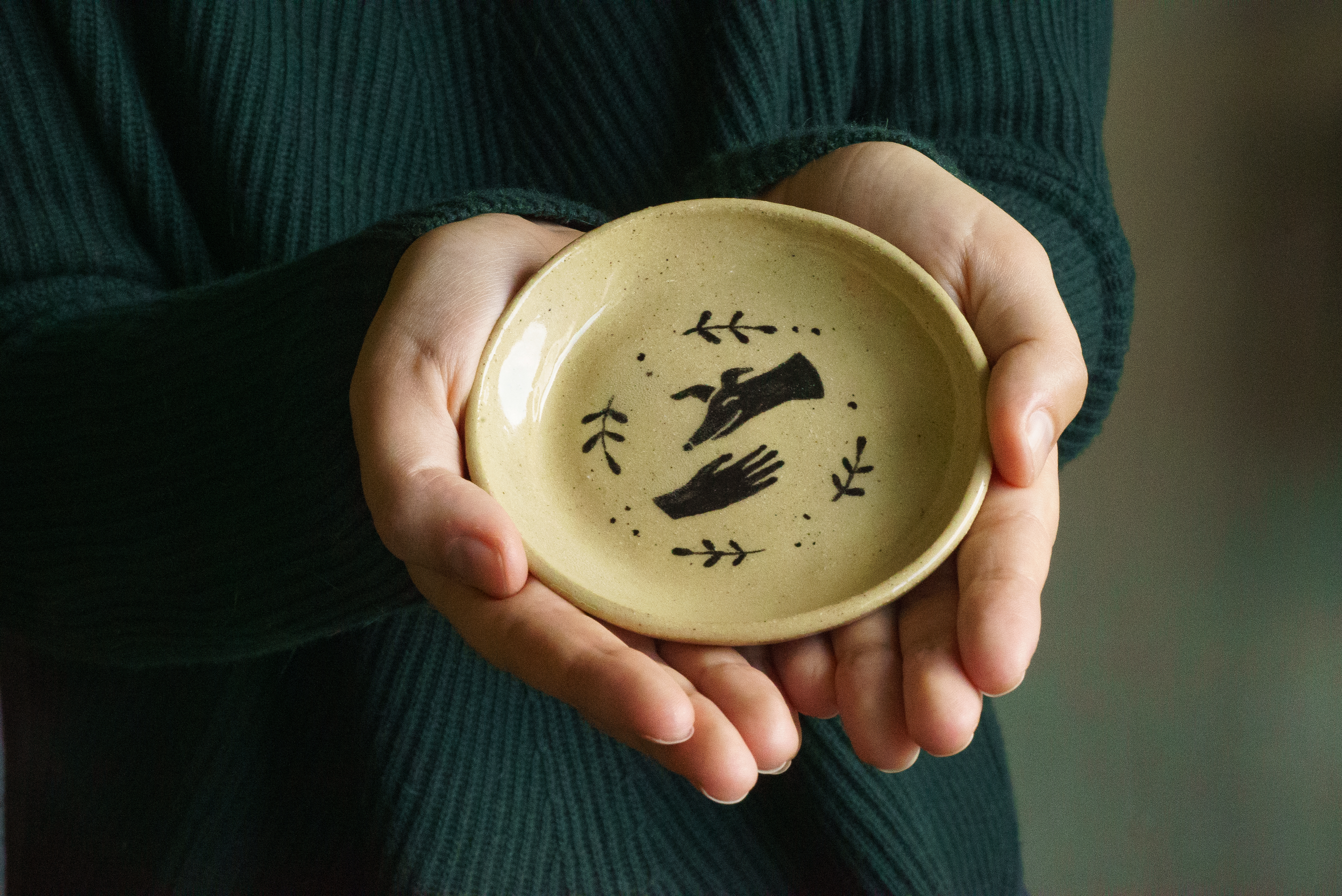 Two hands hold a handmade ceramic dish featuring an illustration of a hand petting a greyhound surrounded by leaves