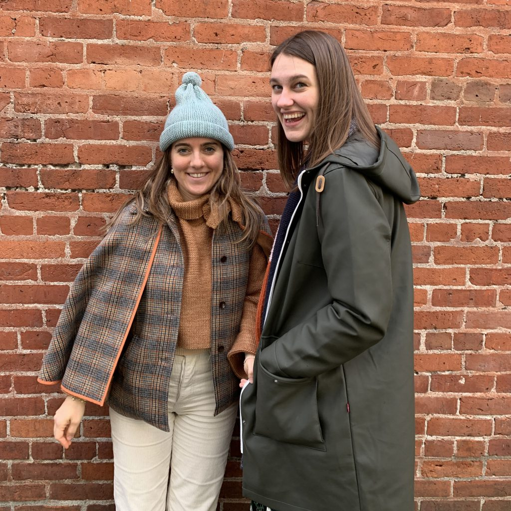 Elisenda and Kaila smiling and laughing in front of a brick wall