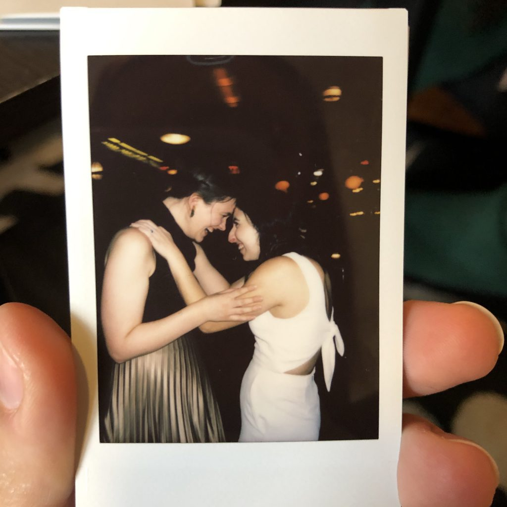 A polaroid of Kaila and Maral at her wedding holding each other and touching foreheads
