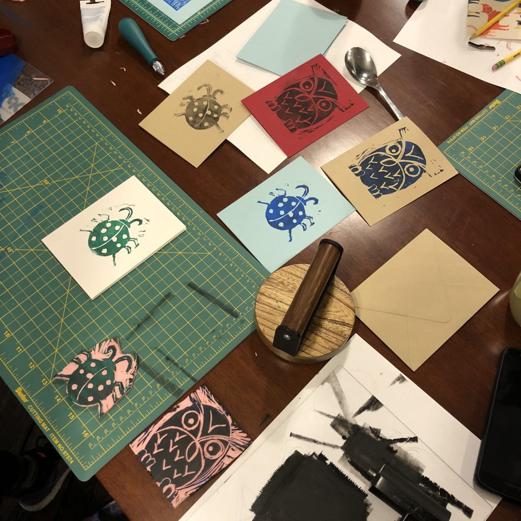 A table filled with creative mess and tools from block printing