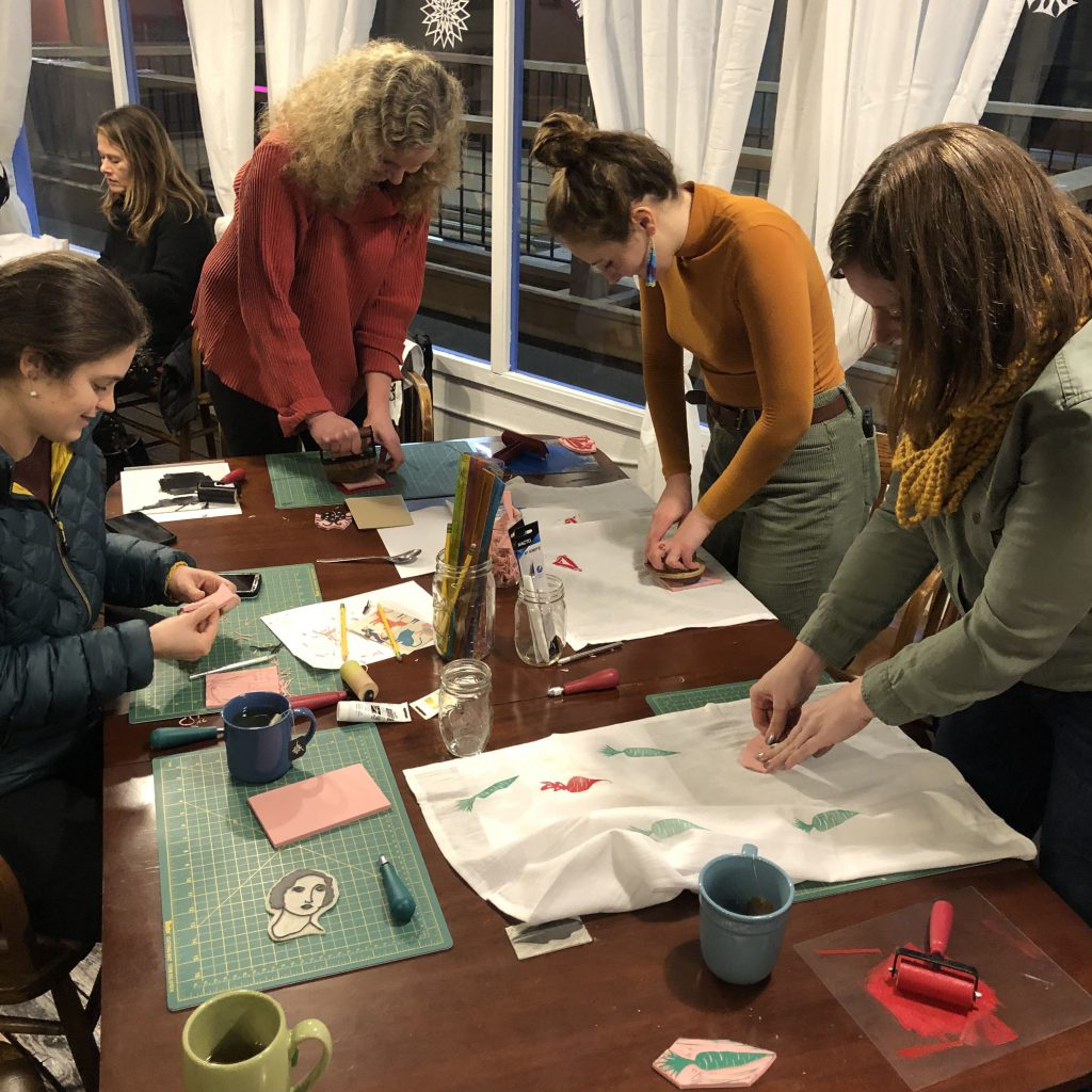 A group of people learning how to block print