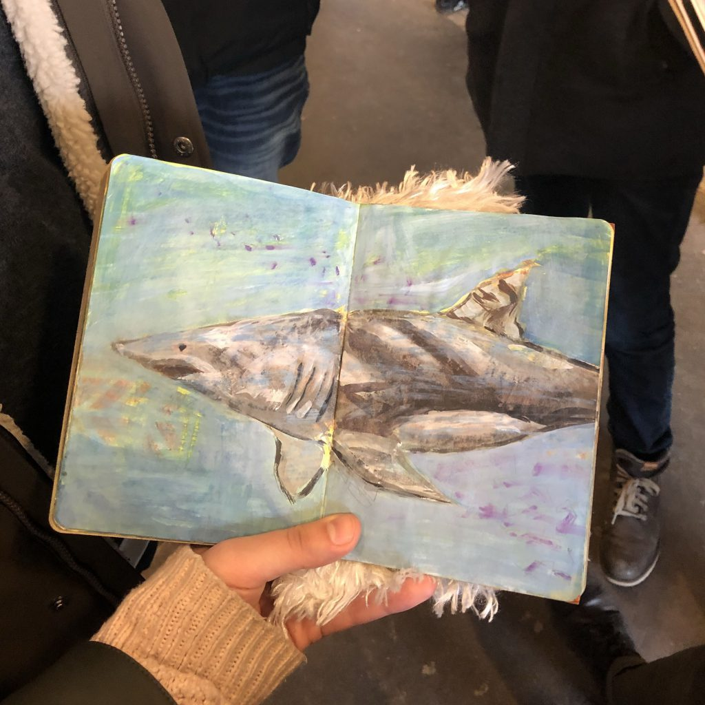 A hand holding open a sketchbook with a drawing of a shark