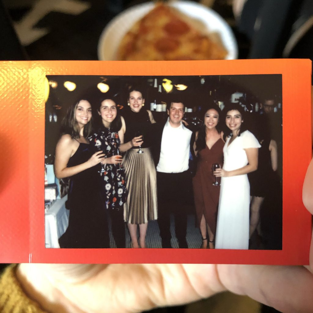 A polaroid with a group of people at a wedding holding drinks