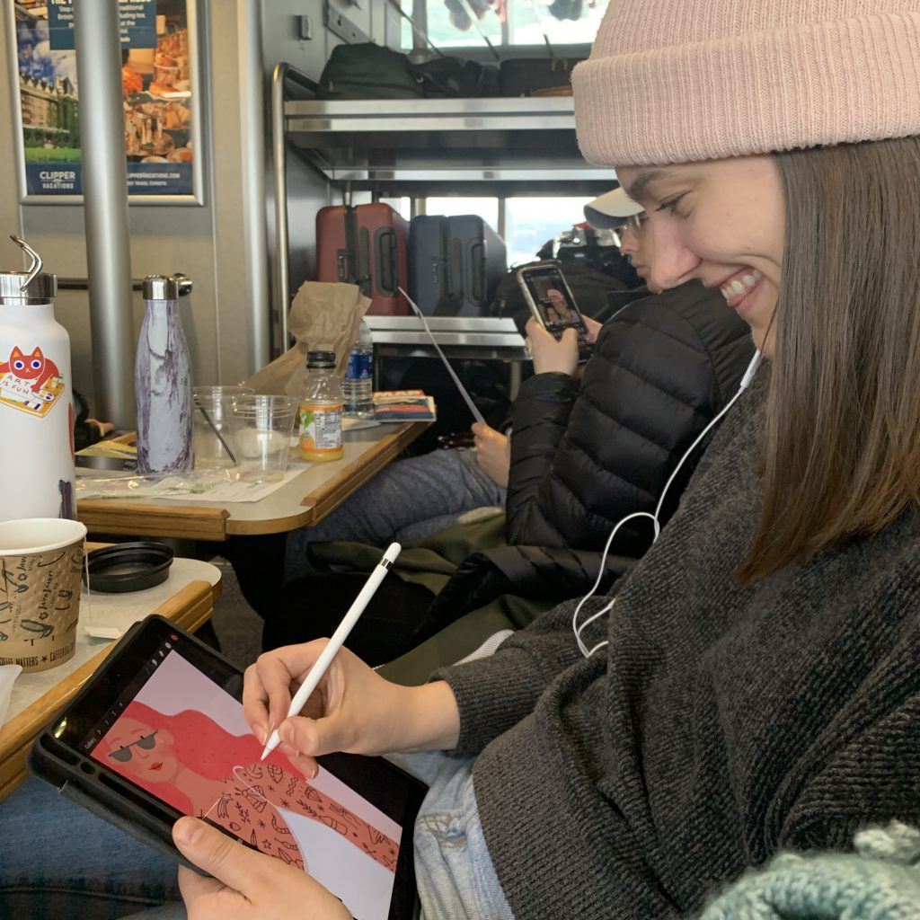 Kaila Elders draws on her ipad on a ferry