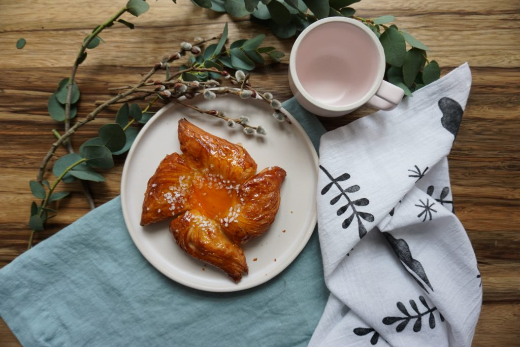 A baked good sits on a ceramic plate next to some greenery, a mug, and handmade block printed linen napkins