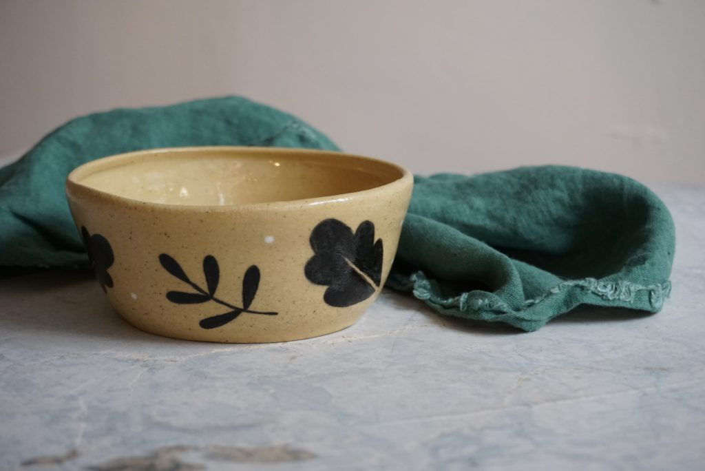 A handmade ceramic bowl with a leaf pattern sits next to a green linen napkin