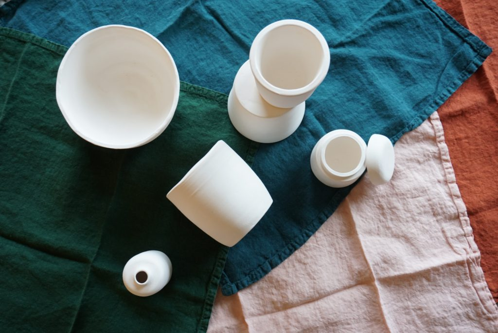 A collection of unglazed ceramic vessels atop colourful linen napkins