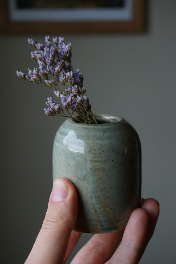 A hand holds up a small vase with purple flowers in it