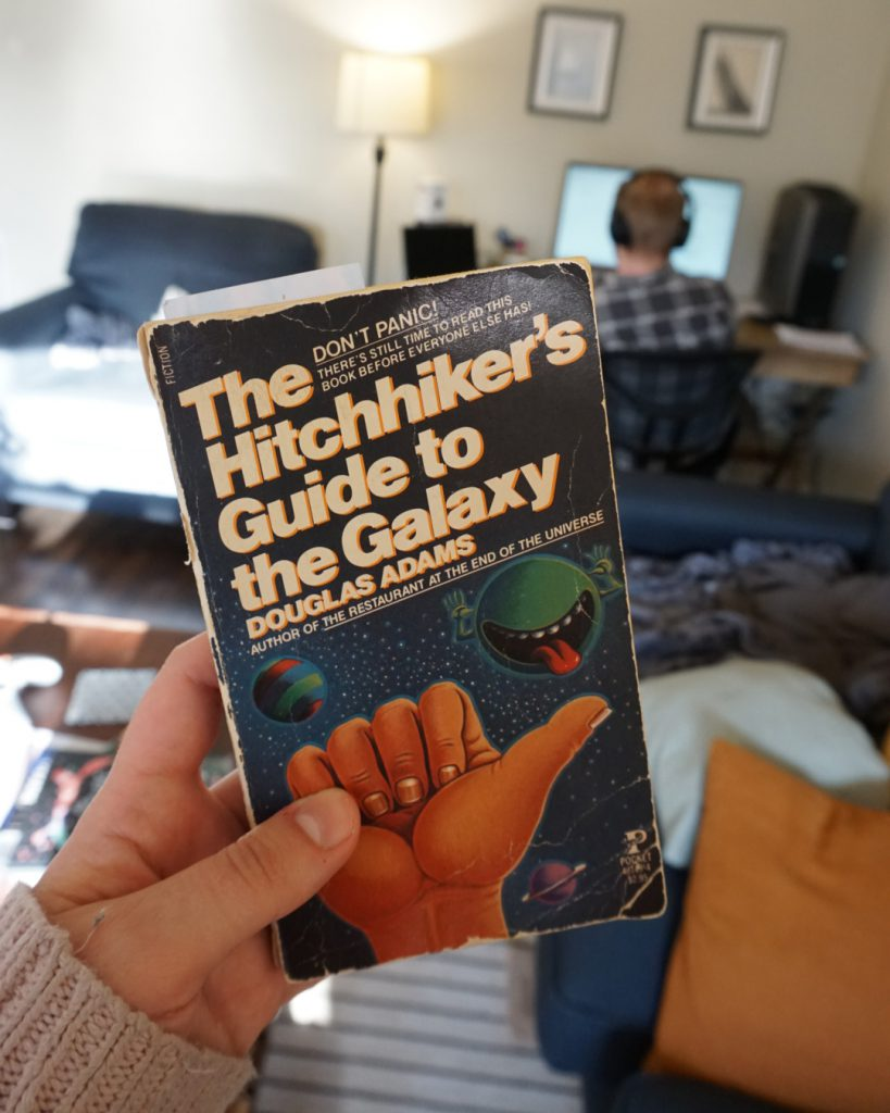 A hand holds a copy of Hitchhiker's Guide to the Galaxy