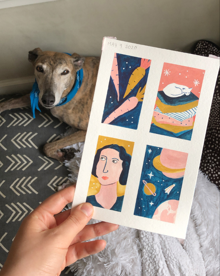 Four small paintings of carrots, a napping cat, a woman's face, and a space scene being held up in front of Greer the greyhound