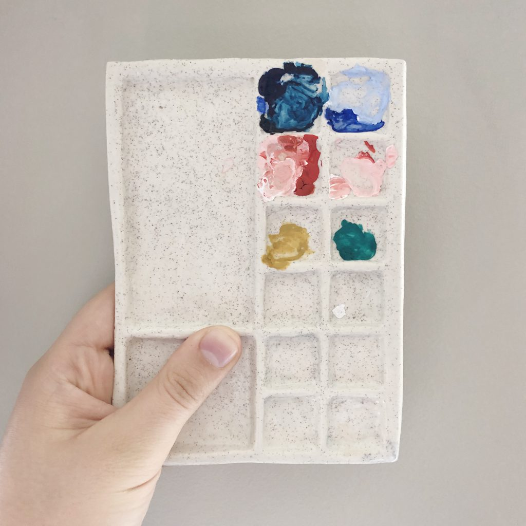 A hand holds a paint palette covered in colourful paints
