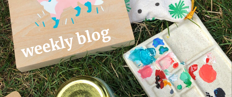 Painting supplies in the grass with the words Weekly Blog written across them
